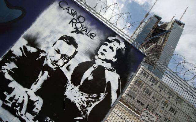 Grafiti en el muro de la nueva ubicación del BCE con Angela Merkel y Mario Draghi como los protagonistas de Casino Royale. / EFE