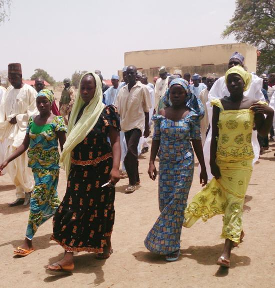 En este Lunes 21 de abril 2014 foto de archivo, cuatro alumnas de la escuela secundaria pública Chibok, que fueron secuestrados por hombres armados y se reunió con sus familias, a pie en Chibok, Nigeria. Un grupo de la sociedad civil, dice miércoles 30 de abril de 2014 que los pobladores han informado de que las puntuaciones de las niñas y mujeres jóvenes que fueron secuestrados recientemente de una escuela en Nigeria se ven obligadas a casarse con los extremistas islámicos. Un senador federal por el área en el noreste de Nigeria quiere el gobierno para obtener ayuda internacional para rescatar a los más de 200 niñas que faltan secuestrados por Boko Haram de una escuela hace dos semanas. (AP Photo / Haruna Umar, archivo)