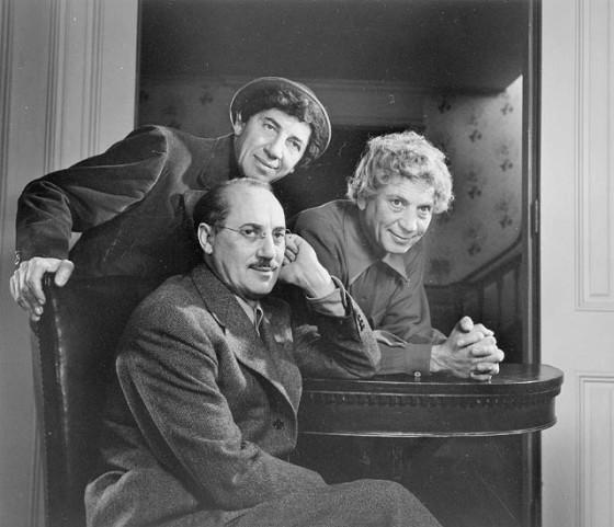 Groucho Marx (sentado) junto a sus hermanos Chico (izquierda) y Harpo (derecha) en 1948.
